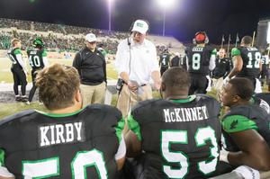 Primary view of object titled '[Mean Green Coach Talking with his Team]'.