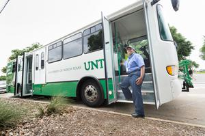 Primary view of object titled '[UNT bus driver posing with her bus]'.