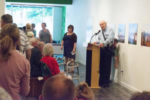 Primary view of object titled '[Ray Bankston Speaking at Podium at Exhibit]'.