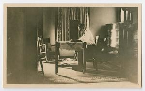Primary view of object titled '[Photo of Byrd Williams Jr. at a table, from the Byrd Williams Jr. album, 1907-1920]'.