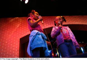 Primary view of object titled '[Two girls singing on stage]'.