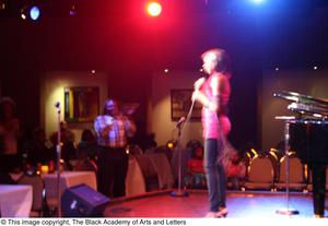 Primary view of object titled '[Rachel Webb singing on stage while Curtis King stands and applauds]'.