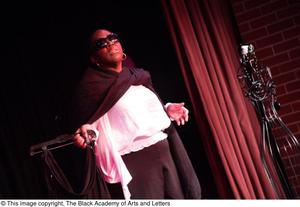 Primary view of object titled '[Performer speaking on stage wearing sunglasses]'.