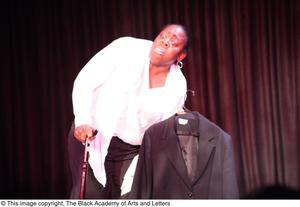 Primary view of object titled '[Performer on stage holding a coat]'.