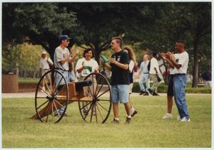 Primary view of object titled '[Students gather around a cannon during North Texas Homecoming activities]'.