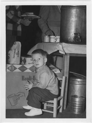 Primary view of object titled '[Child seated at North Texas 1956 Homecoming alumni luncheon]'.