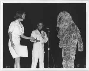 Primary view of object titled '[Two cheerleaders and mascot at North Texas Homecoming bonfire, 1964]'.