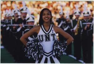 Primary view of object titled '[North Texas dancer and marching band at 1997 Homecoming halftime show, #3]'.