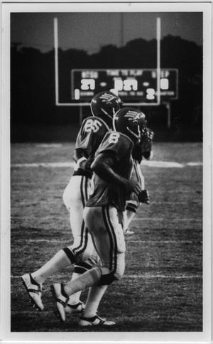 Primary view of object titled '[Two North Texas Players Walk Across the Field]'.