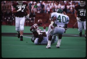 Primary view of object titled '[North Texas Football Player Tackles an Aggie, 1991]'.