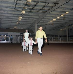 Primary view of object titled '[Parents and Two Children In a Roping Arena]'.