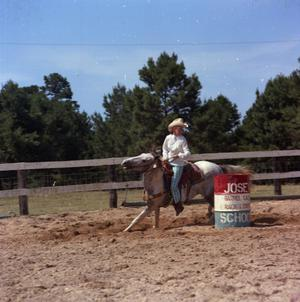 Primary view of object titled '[Woman Barrel Racing on Gray Horse]'.