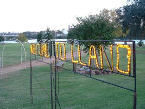 "Primary view of object titled '[Yellow illuminated ""Welcome to Llano"" sign]'."