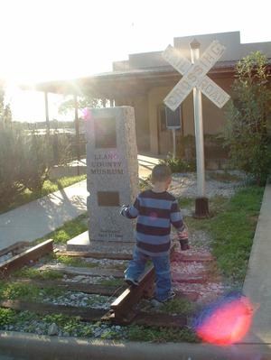 "Primary view of object titled '[Young boy near ""Llano County Museum"" sign]'."