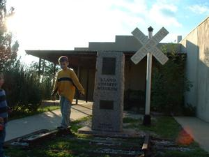 "Primary view of object titled '[Boy playing in front of ""Llano County Museum"" sign]'."