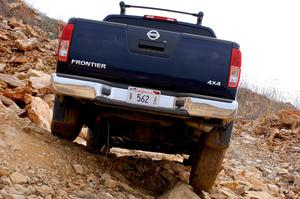 Primary view of object titled '[Back of a Nissan Frontier truck driving down a rocky slope]'.