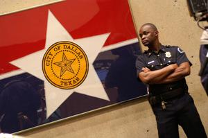Primary view of object titled '[A Police Officer Stands Beside a Framed City of Dallas Flag, Looking to the Right]'.