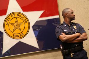 Primary view of object titled '[A Police Officer Stands Beside a Framed City of Dallas Flag and Looks to the Side]'.