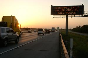 Primary view of object titled '[An Amber Alert sign alerts travelers about a kidnapped child]'.