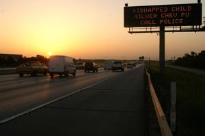 Primary view of object titled '[Vehicles pass an Amber Alert sign beside the highway at sunset]'.