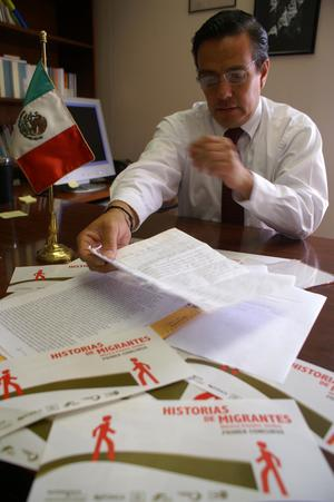 Primary view of object titled '[Oscar Solis Flores moving papers on his desk]'.