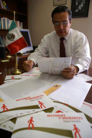 Primary view of object titled '[Oscar Solis Flores reading papers at his desk]'.