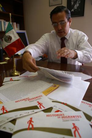 Primary view of object titled '[Oscar Solis Flores viewing papers on his desk]'.