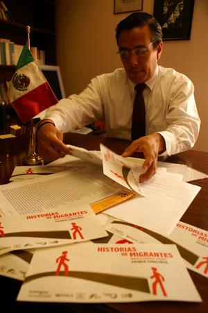 Primary view of object titled '[Oscar Solis Flores handling papers on his desk]'.