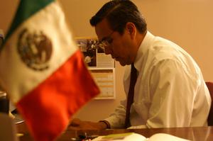 Primary view of object titled '[Oscar Solis Flores with Mexican flag in foreground]'.