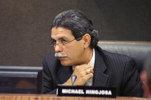 Primary view of object titled '[Michael Hinojosa sitting and grasping his collar]'.