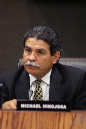 Primary view of object titled '[Michael Hinojosa sitting at table with nameplate and microphone]'.