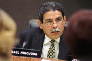 Primary view of object titled '[Michael Hinojosa with a microphone and nameplate bearing his name]'.
