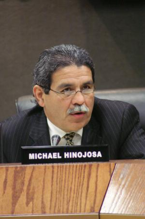 Primary view of object titled '[Michael Hinojosa sitting behind wooden ledge bearing his nameplate]'.