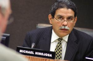 Primary view of object titled '[Michael Hinojosa sitting behind a nameplate bearing his name]'.