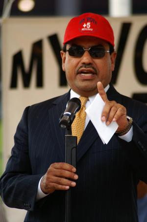 Primary view of object titled '[Close-up of Luis de la Garza speaking at microphone wearing red hat]'.