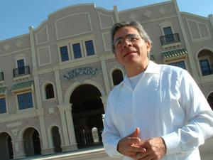 Primary view of object titled '[Jose Legaspi with hands clasped in front of Fort Worth Mercado]'.