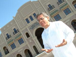 Primary view of object titled '[Jose Legaspi standing in front of Fort Worth Mercado with palms turned upward]'.