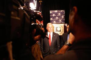Primary view of object titled '[Distance image of Howard Dean in front of NALEO seal]'.