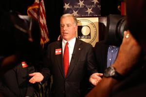 Primary view of object titled '[Howard Dean speaking in front of NALEO seal with hands outstretched]'.
