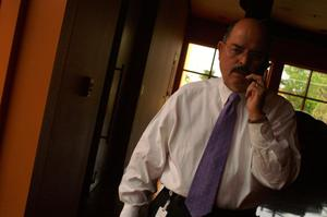 Primary view of object titled '[Front view of Hector Flores speaking on cellular phone]'.