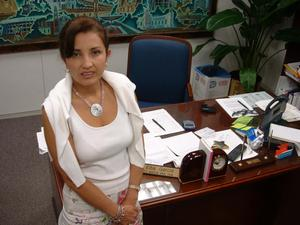Primary view of object titled '[Elba Garcia standing in front of her desk]'.