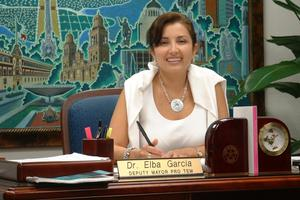 Primary view of object titled '[Elba Garcia sitting at her desk]'.