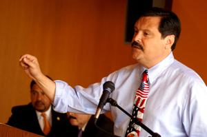 Primary view of object titled '[Domingo Garcia speaking into microphone with arm raised]'.