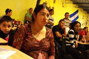 Primary view of object titled '[Woman listens to speaker in the El Salvador Restaurant]'.
