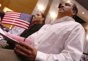 Primary view of object titled '[Man with a small U.S. flag and papers in his hands sits during a citizenship ceremony]'.