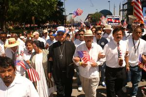 Primary view of object titled '[Immigration protesters march with priest]'.