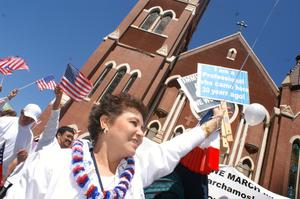 Primary view of object titled '[Female protester with sign marches past Cathedral Santuario de Guadalupe in Dallas]'.
