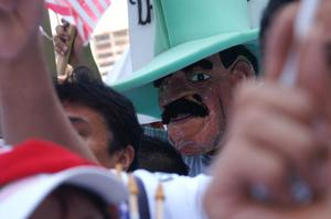 Primary view of object titled '[Immigration protester wearing mask and hat]'.