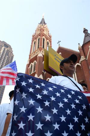 Primary view of object titled '[Male protester marches past Cathedral Santuario de Guadalupe in Dallas]'.
