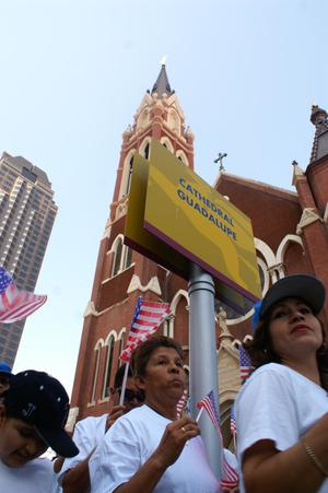 Primary view of object titled '[Immigration protesters march past Cathedral Santuario de Guadalupe in Dallas]'.
